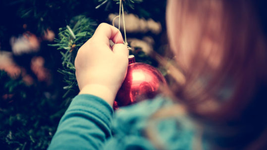 48555948 - little girl is decorating christmas tree with home made ornaments in retro filter effect